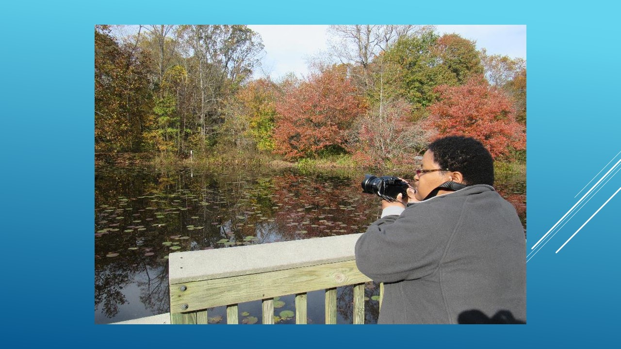 Photo of woman with developmental disabilities taking photos at a pond in fall