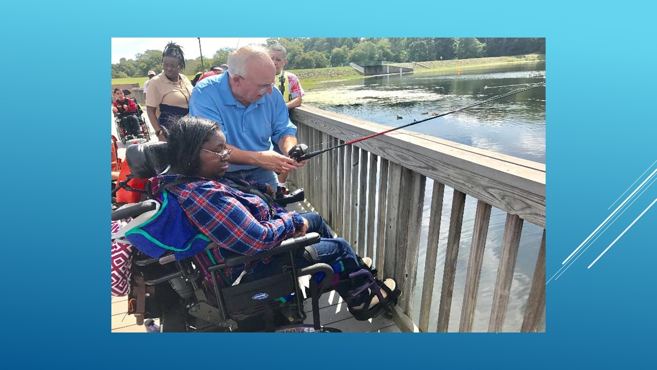 Photo of a woman in a wheelchair being shown how to fish at a pond