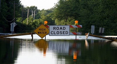 A flooded street with a road closed sign.