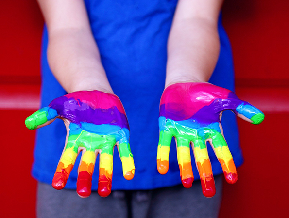 child hands painted with rianbow