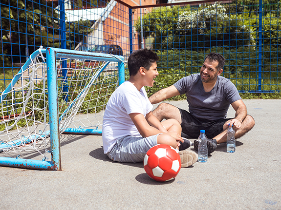adult and teen sitting on soccer field talking