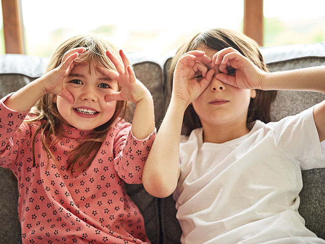 two children on sofa holding fingers over eyes