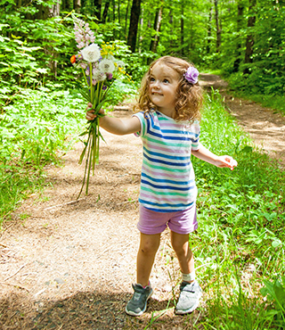 child holding wildflowers