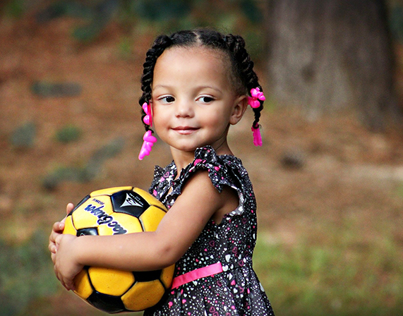 child smiling holding soccer ball in arms