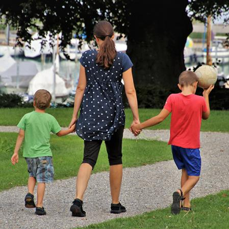 parent and two children holding hands and walking outside