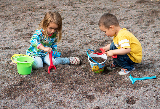two children playing outside in sandbox
