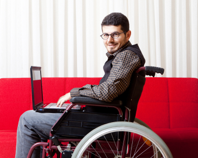 male-wheelchair-user-at-work-using-laptop