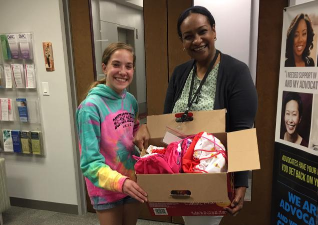person giving care package to DVAC person accepting package