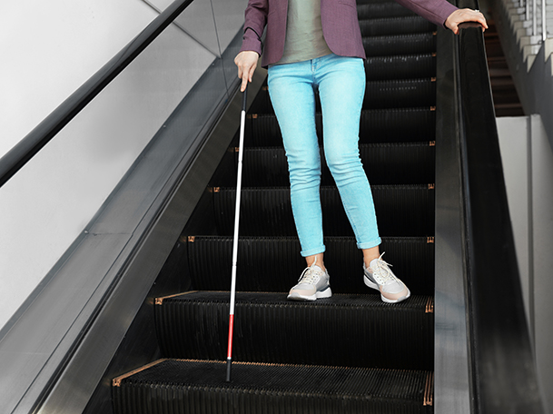 person standing on escalator with cane in hand