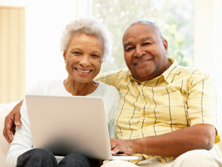 older adult couple using laptop