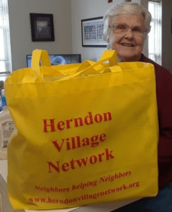 A resident receives groceries from Herndon Village Network