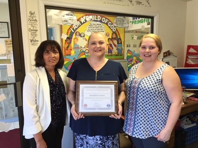 Springfield Academy Director Jennifer Schwitz and Administrative Support Professional Angela Todd accept a certificate of recognition from Christine Carlock with the Fairfax County Health Department.