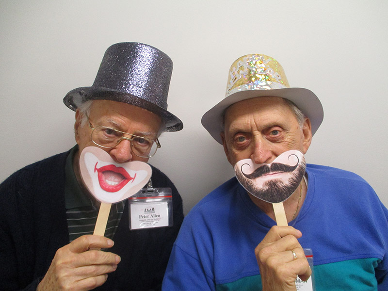 Two male ADHC participants wear a hat and smiley mouth mask for World Smile Day