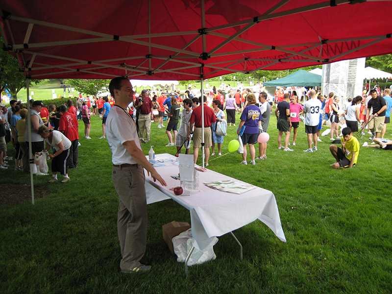 Volunteer staffs an MRC table at an outdoor event