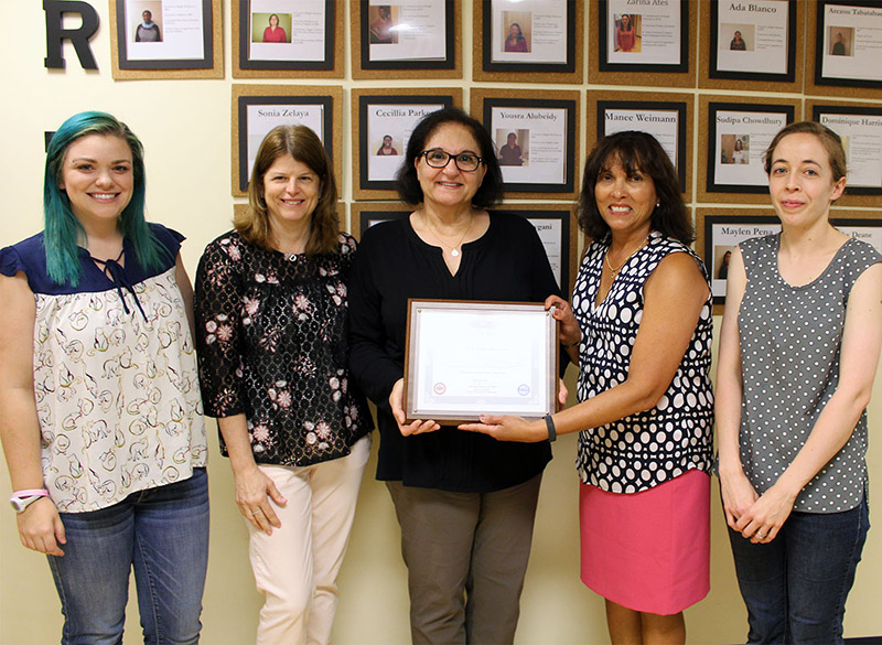 Four Bright Horizons staff members accept a certificate of recognition from Christine Carlock