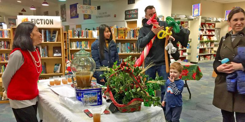 Photo of staff and families at a library holiday open house