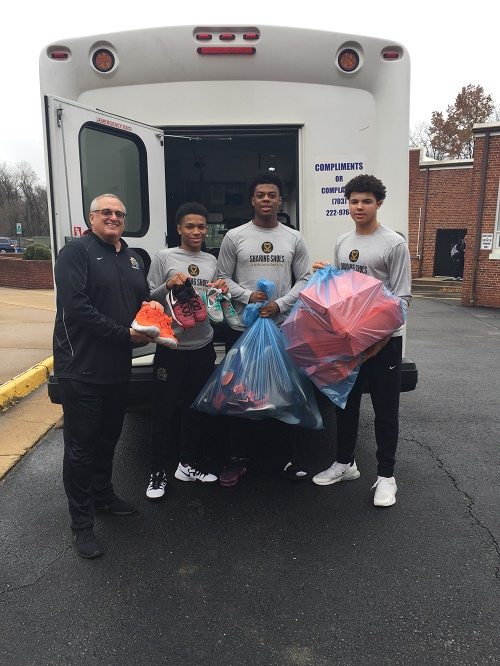 Coach and students pose with donated shoes.