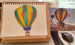 Photo showing a painting of an air balloon and the photo it based on