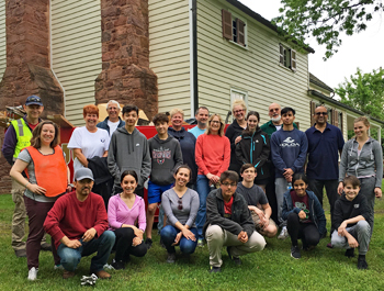 Volunteers pose in front of a restored house.