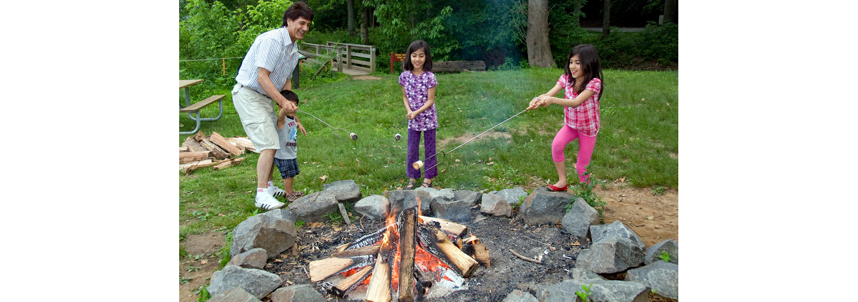 A family cooks a meal on sticks over a campfire