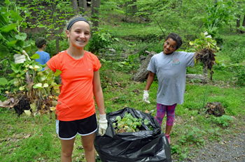 Two young girls display their bags of removed invasive plants