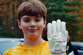 A young boy holds up his gloved hand with I.M.A. Volunteer stitched on it
