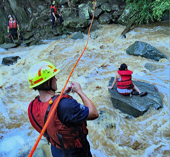 Stranded person is rescued after quick rising waters trapped her midstream.