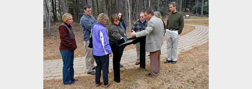 A guide talks to a group of visitors about an interpretive sign at Ox Hill.