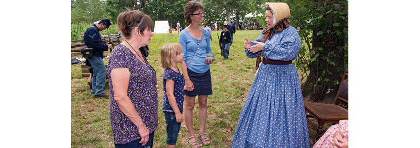 Costumed female re-enactor speaks with park visitors