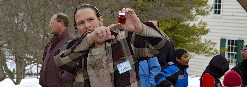 Man holds tiny bottle of boiled down maple syrup