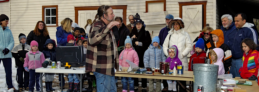 Visitors watch a syrup boil down demonstration