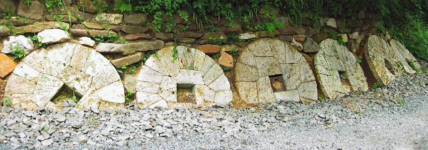 Several millstones displayed on a hillside