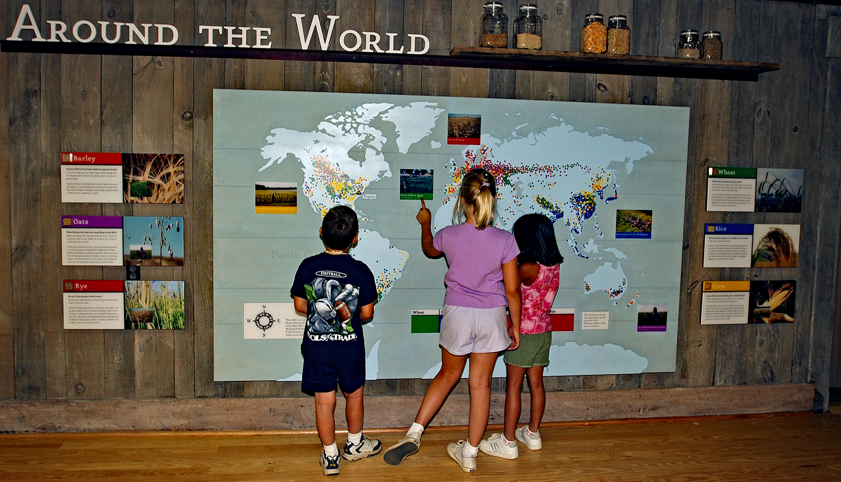 Children look at a map of where grains grow around the world
