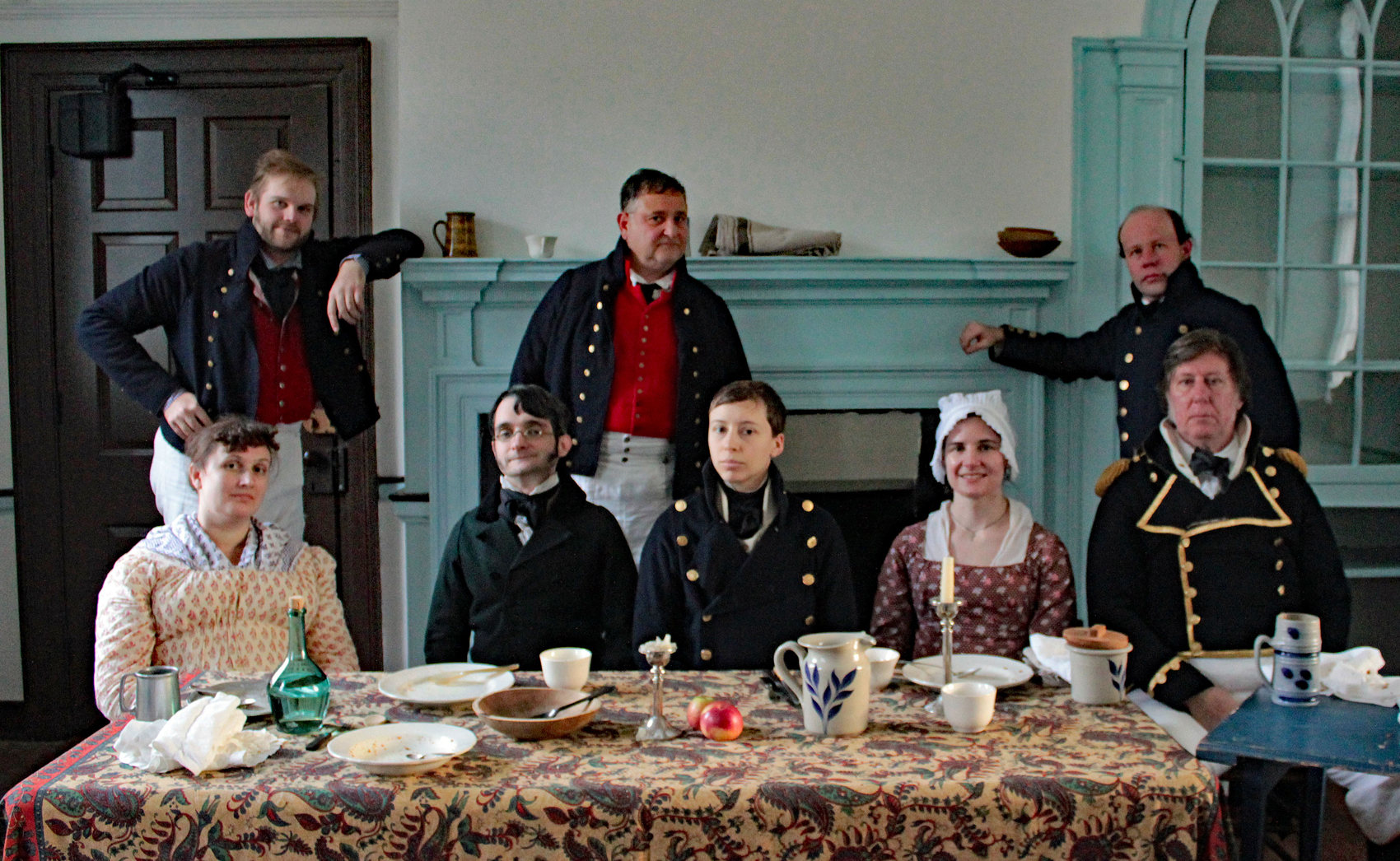 A Ship's Company crew sits around a dinner table at a re-enactment
