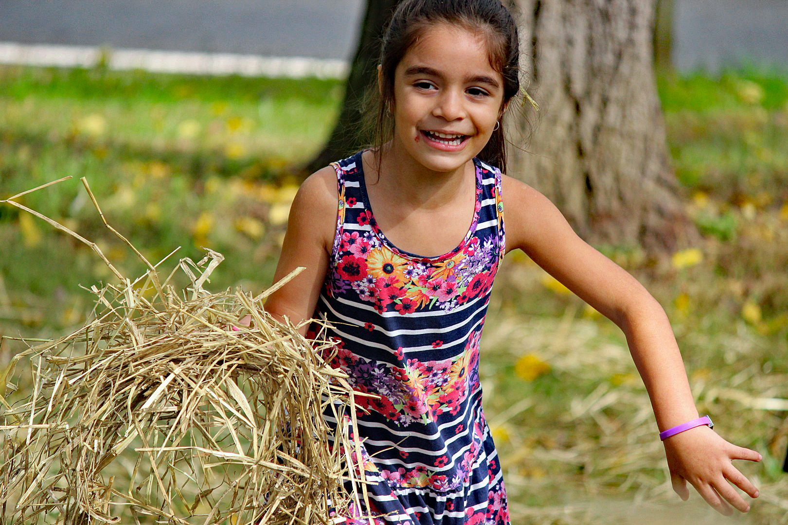 A young girl smiles as she gathers straw to stuff in a scarecrow