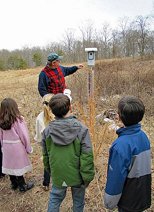 Naturalist stands next to a bird house on a field trip with children