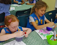 Two Girl Scouts work on crafts at a table