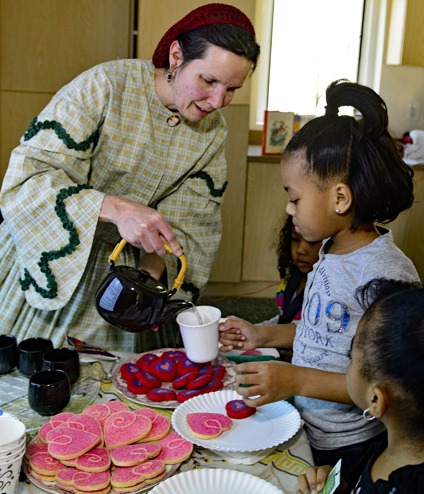 Docent in costume pours tea for a young child