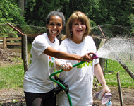 Two ECLP volunteers play with a water hose while working in a garden