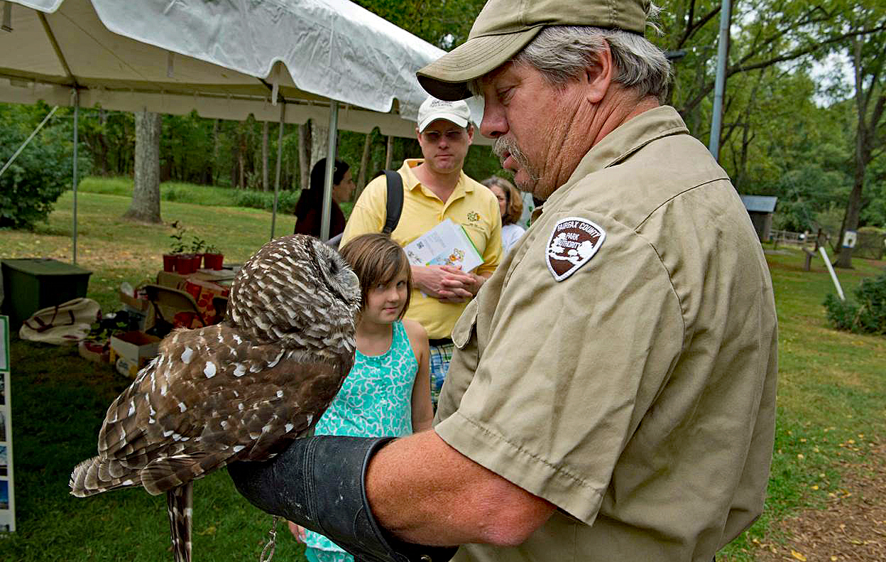 Naturalist holds an owl on his arm while a young girl looks on