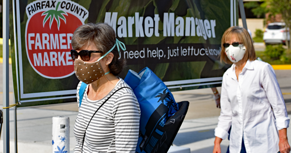 Two shoppers with face coverings wait in line at Burke Farmers Market