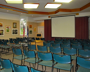 Chairs arranged in rows and a viewing screen in Green Spring's multi-purpose room.