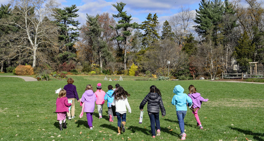 Girl Scouts run across a grassy field at Green Spring