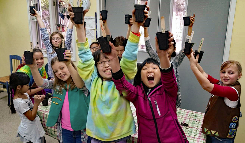 A troop of Girl Scouts raise high pots with seeds they have planted