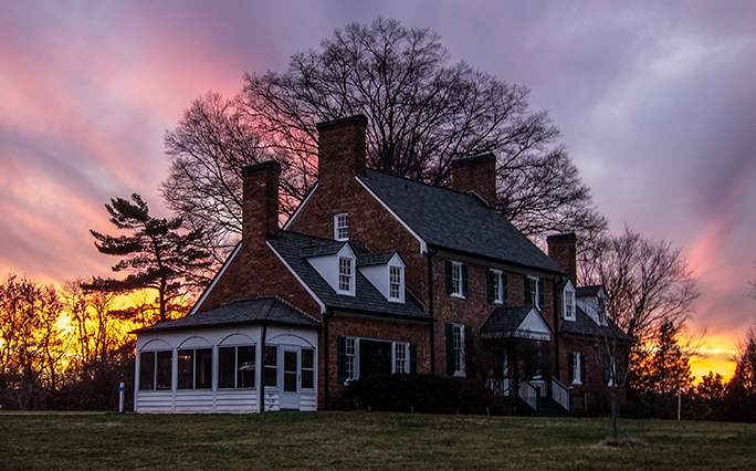 The sun sets behind Green Spring's Historic House and lawn