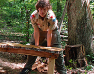 Boy Scout building a bench out of tree stumps