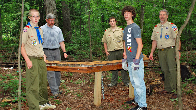 Several scouts stand with a bench they built for Nature Playce at Hidden Oaks