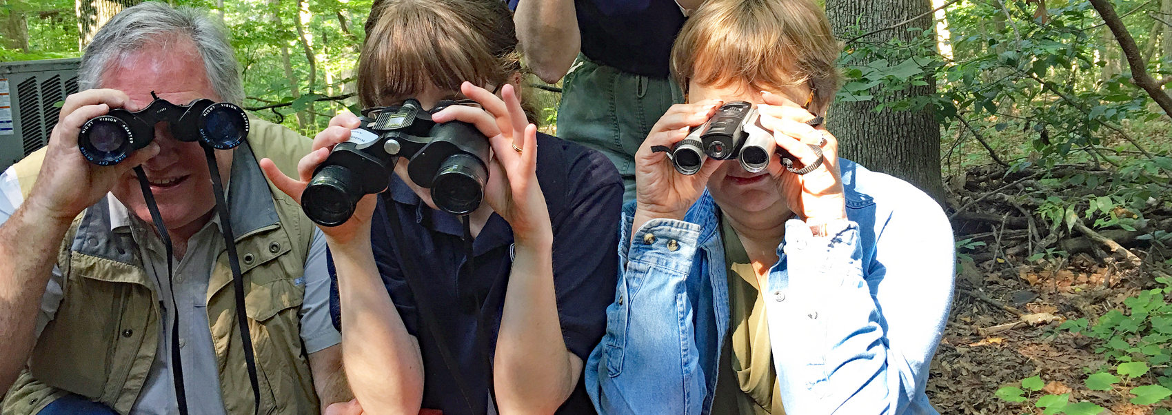 Three staff members post with binoculars