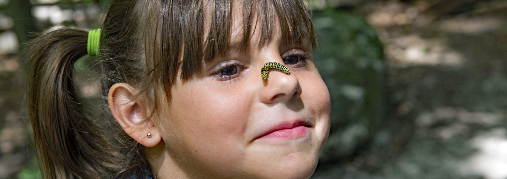 A caterpillar crawls across a young girl's nose