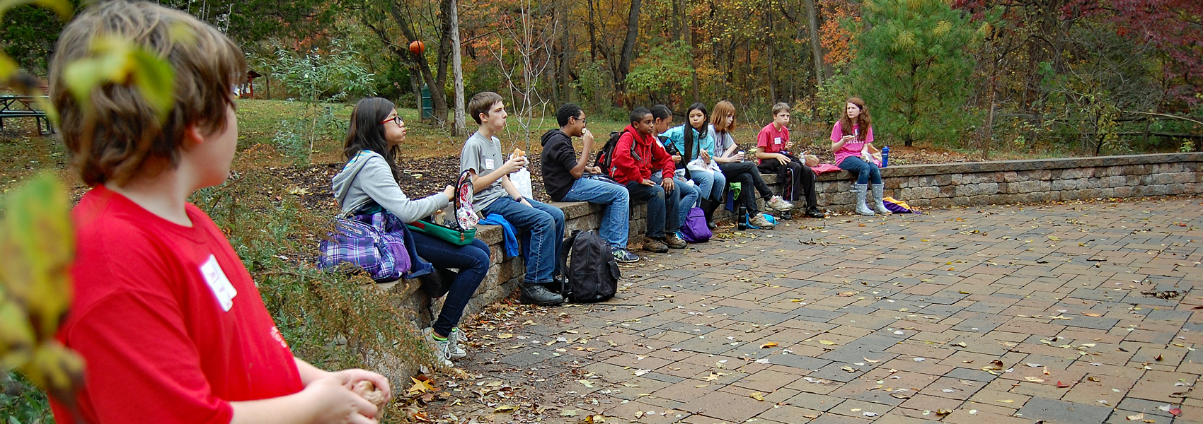 Students sit on a wall and take a lunch break during a class